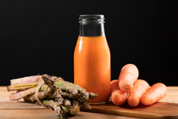 Vista frontal de zanahorias y espárragos con batido