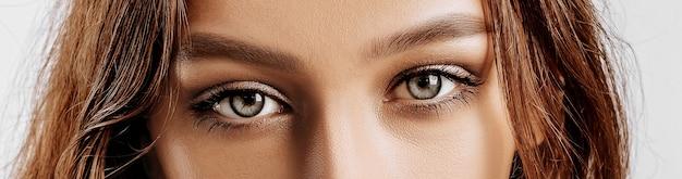 Vista de una hermosa joven morena. ojos verdes femeninos con maquillaje natural. la mujer mira a la cámara.