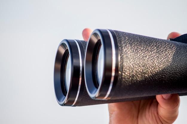 Vista de un hombre con binoculares mirando el horizonte del mar.