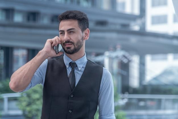Vista de un hombre de negocios atractivo joven con smartphone