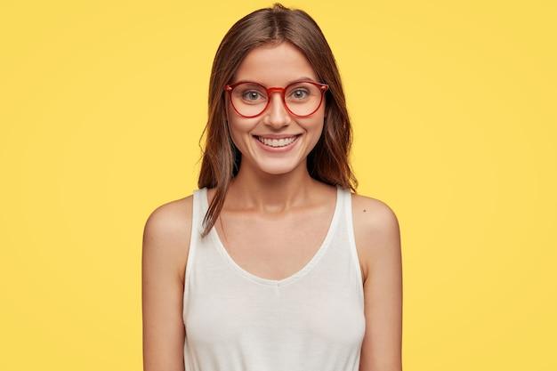 Vista horizontal de la alegre mujer morena emotiva con gafas ópticas y chaleco blanco