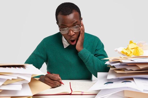 Vista horizontal del asombrado hombre negro trabaja con documentos, escribe notas en el bloc de notas, tiene una expresión facial estupefacta, usa anteojos grandes
