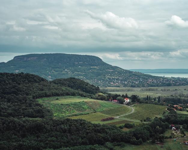 La vista horizontal de los campos y colinas en la orilla de un lago en un día nublado