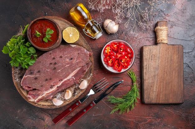 Vista horizontal de carne roja en bandeja de madera y salsa de tomate verde ajo y botella de aceite de pimienta picada y tabla de cortar sobre fondo oscuro