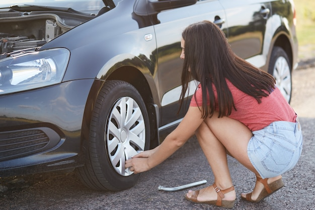 La vista horizontal de una conductora experimentada intenta reparar una llanta desinflada, usa un equipo especial, resuelve problemas con la rueda, plantea al costado de la carretera, no puede continuar conduciendo, ha dañado la rueda, cambia el caucho