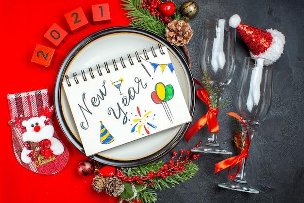 Vista horizontal del cuaderno con escritura de año nuevo y dibujos, platos de cena, accesorios de decoración, ramas de abeto, calcetín de navidad, copas de vidrio en una mesa oscura