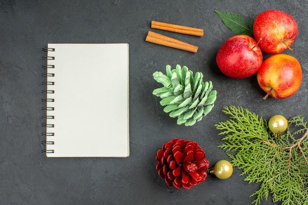 Vista horizontal del cuaderno y manzanas frescas, canela, limones y accesorios de decoración sobre fondo negro