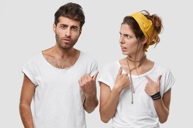 Vista horizontal de dos dama disgustada y su novio en el interior contra el espacio en blanco