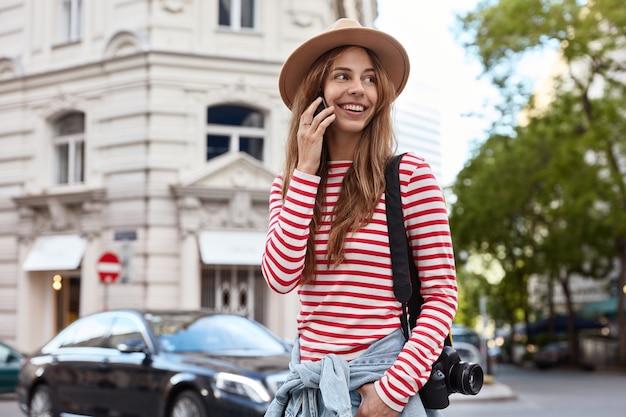 Vista horizontal de feliz joven mujer europea habla por teléfono moderno, mira a un lado, viste un jersey de rayas