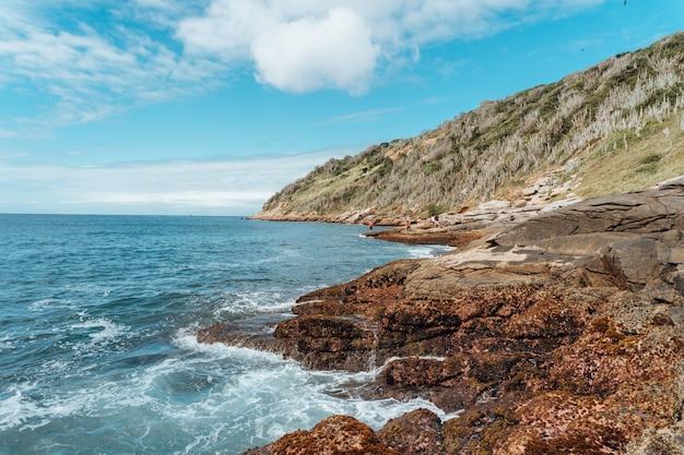 La vista horizontal de las formaciones rocosas en la playa de río