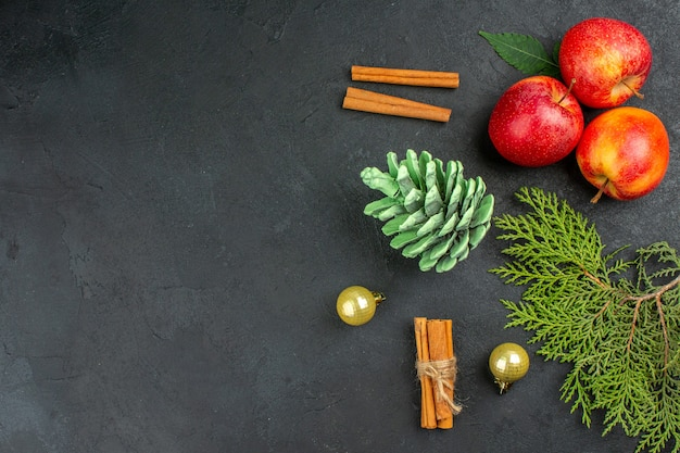 Vista horizontal de manzanas frescas, canela, limones y accesorios de decoración en mesa negra
