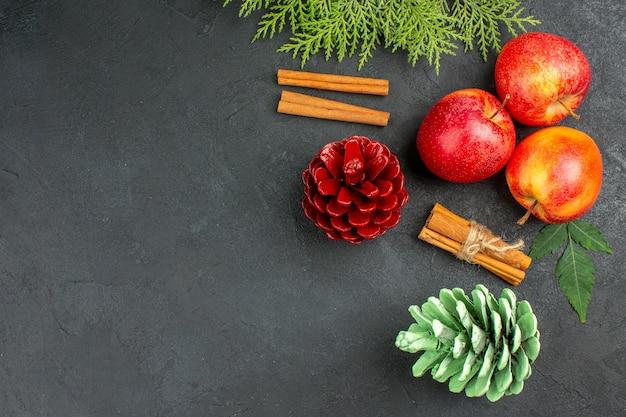 Vista horizontal de manzanas frescas, canela, limones y accesorios de decoración sobre fondo negro
