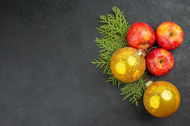 Vista horizontal de manzanas frescas orgánicas naturales y accesorios de decoración sobre fondo negro
