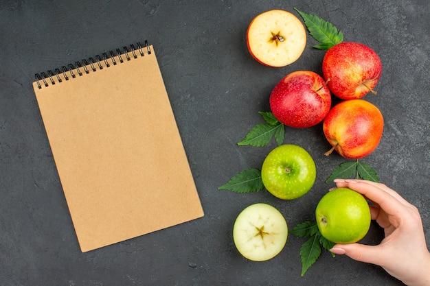 Vista horizontal de manzanas y hojas naturales frescas enteras y cortadas y cuaderno sobre fondo negro