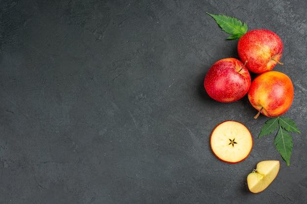 Vista horizontal de manzanas rojas orgánicas naturales frescas enteras y cortadas con hojas verdes sobre fondo negro