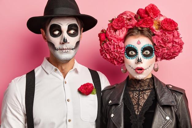 Vista horizontal de la pareja sorprendida con cara de miedo, calaveras de azúcar pintadas y sonrisas, celebran juntos el carnaval popular