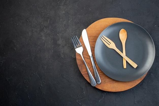 Vista horizontal de la placa de color oscuro y juegos de cubiertos de madera inoxidable sobre una tabla de cortar redonda marrón sobre fondo negro con espacio libre