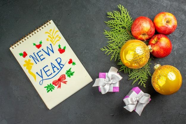 Vista horizontal de regalos y manzanas frescas orgánicas naturales y accesorios de decoración con inscripción de año nuevo sobre fondo negro