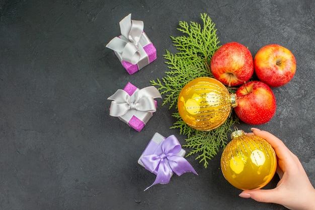 Vista horizontal de regalos y manzanas frescas orgánicas naturales y accesorios de decoración en el lado izquierdo sobre fondo negro