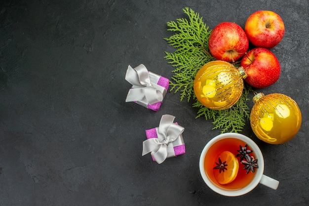 Vista horizontal de regalos y manzanas frescas orgánicas naturales y accesorios de decoración una taza de té sobre fondo negro