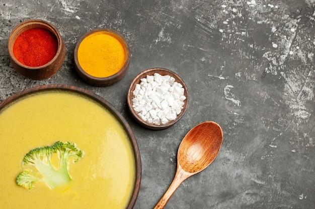 Vista horizontal de sopa cremosa de brócoli en un recipiente marrón y diferentes especias en mesa gris