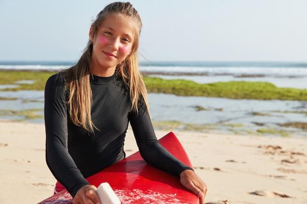 Vista horizontal de surfista profesional se prepara para el surf, tabla de cera con cera, quiere demostrar doble hilandero