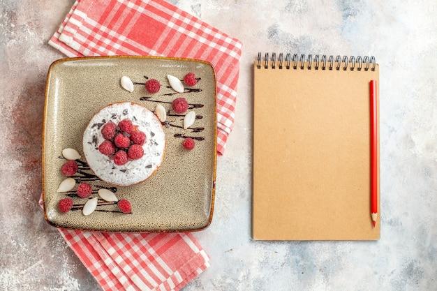 Vista horizontal de tarta recién horneada con frambuesas y cuaderno con lápiz