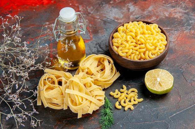 Vista horizontal de tres porciones crudas de espaguetis y botella de aceite verde limón en la tabla de colores mezclados