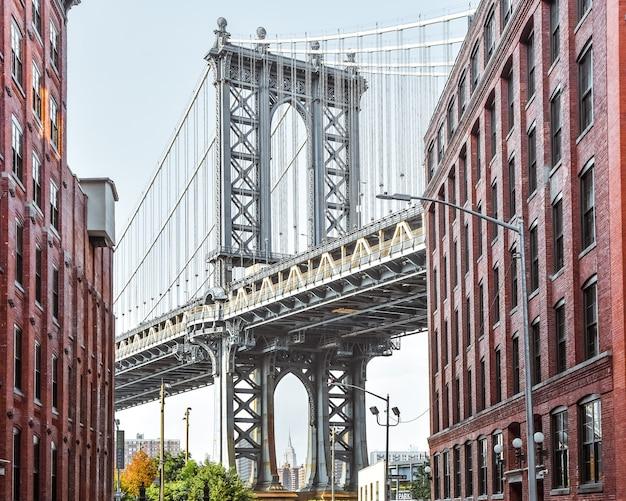 Vista icónica del puente de manhattan desde washington street. edificios de la calle de ladrillo rojo que conducen al puente al anochecer. brooklyn. nueva york, estados unidos.