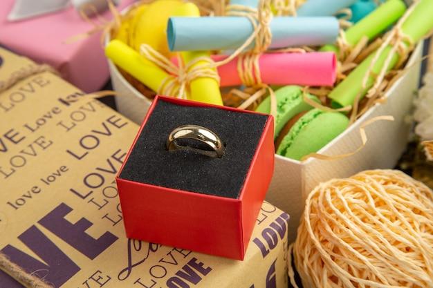Vista inferior del anillo en la caja de corazón con notas adhesivas enrolladas y macarons envueltos regalos sobre fondo oscuro