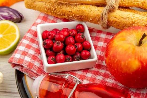 Vista inferior de las bayas de rosa de perro en un tazón de pan de manzana botella roja sobre una servilleta en un plato redondo sobre una mesa blanca