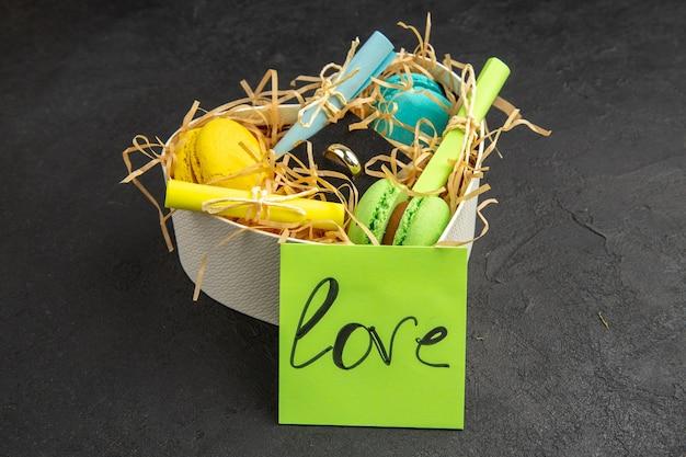 Vista inferior caja en forma de corazón con macarons enrollados notas adhesivas amor escrito en una nota adhesiva sobre fondo oscuro