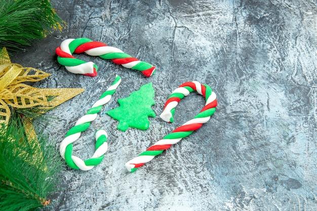 Vista inferior caramelos de navidad adornos de navidad sobre fondo gris con espacio libre