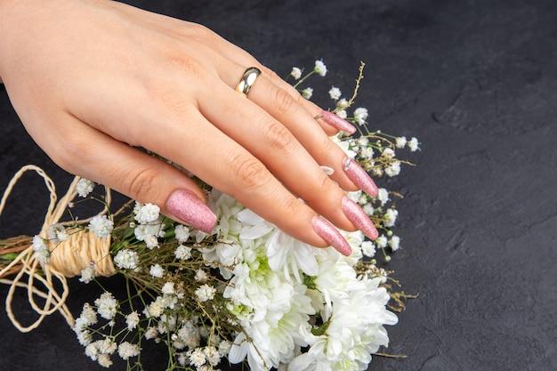 Vista inferior concepto de propuesta de matrimonio mano femenina con anillo de compromiso flores sobre fondo oscuro