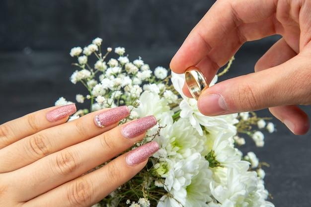 Vista inferior concepto de propuesta de matrimonio manos del hombre colocando el anillo de bodas en la mano de la mujer flores de boda blancas