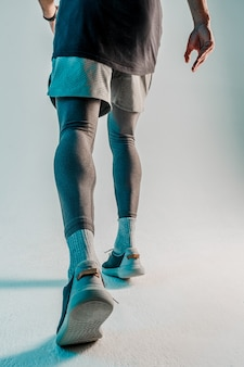 Vista inferior del corredor. deportista usa uniforme deportivo. aislado sobre fondo turquesa. sesión de estudio