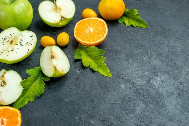 Vista inferior cortar manzanas y mandarinas cumcuat hojas en el espacio libre de la mesa oscura