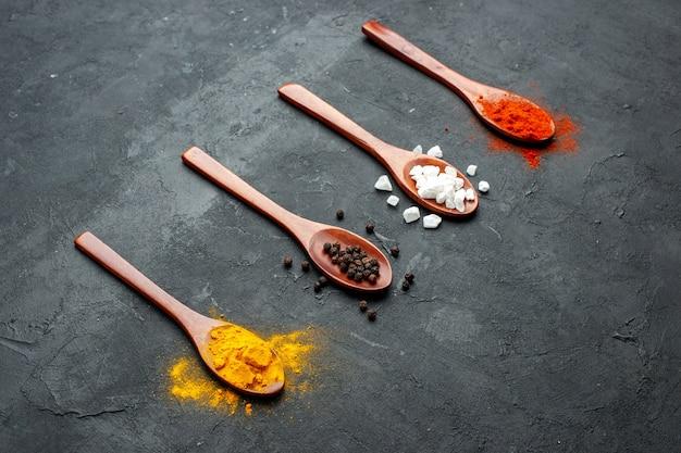 Vista inferior de cucharas de madera de fila diagonal con cúrcuma, pimienta negra, sal sae, pimienta roja en polvo sobre superficie negra