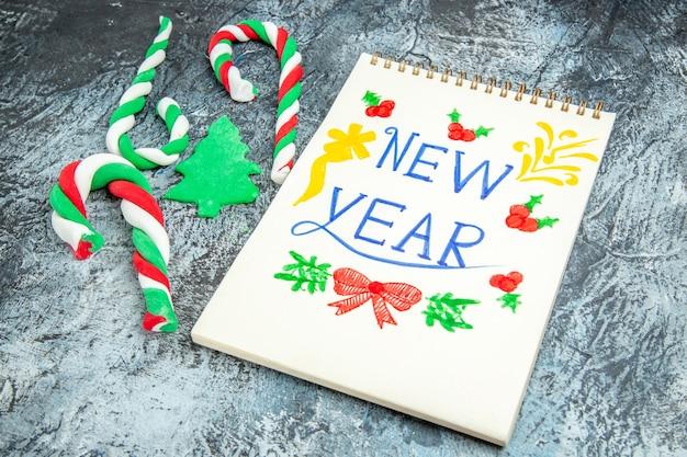 Vista inferior de dulces de navidad año nuevo escrito en el bloc de notas sobre fondo gris