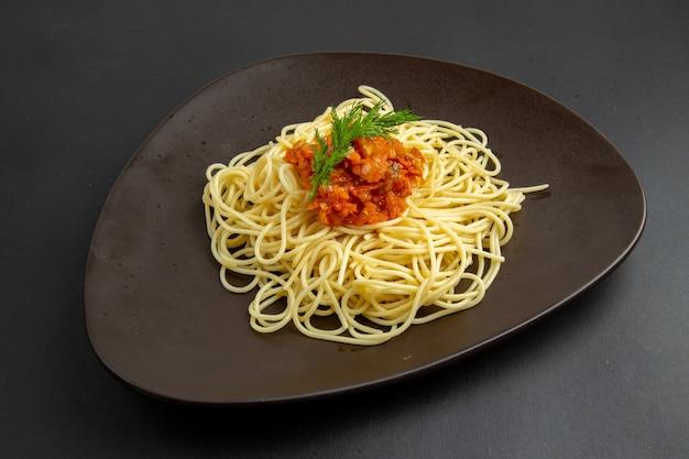 Vista inferior de espaguetis con salsa en un plato sobre fondo negro