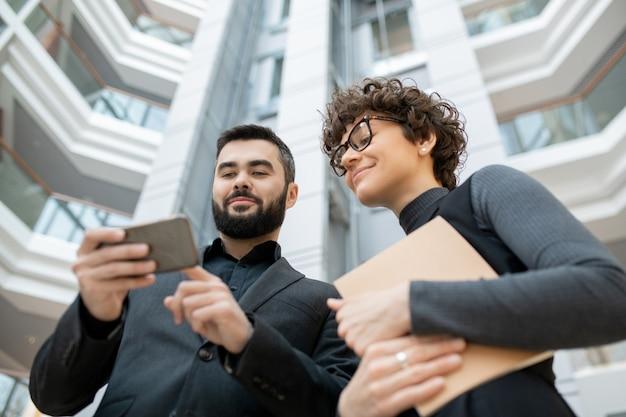 Vista inferior de especialistas en marketing exitosos que utilizan teléfonos inteligentes mientras miran estadísticas en las redes sociales