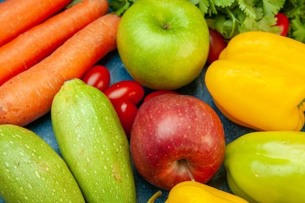 Vista inferior frutas y verduras pimientos manzanas calabacín zanahoria cilantro en mesa azul