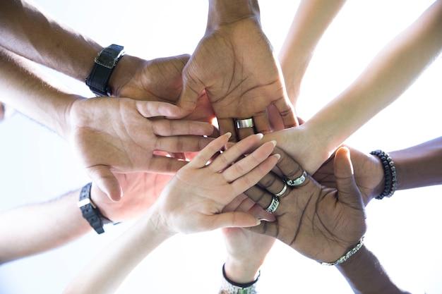 Vista inferior, gente poniendo las manos juntas.