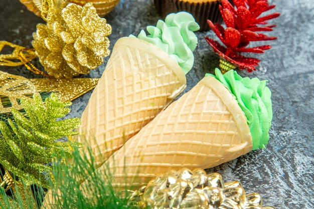 Vista inferior helados adornos navideños de la magdalena del árbol de navidad sobre fondo gris