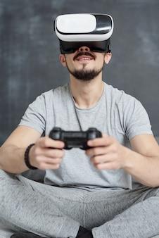 Vista inferior del hombre barbudo en ropa de casa emocionado por el videojuego virtual que usa un joystick en gafas de realidad virtual