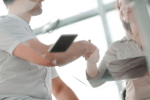 Vista inferior. hombre de negocios y empresaria dándose la mano sobre el escritorio. concepto de cooperación