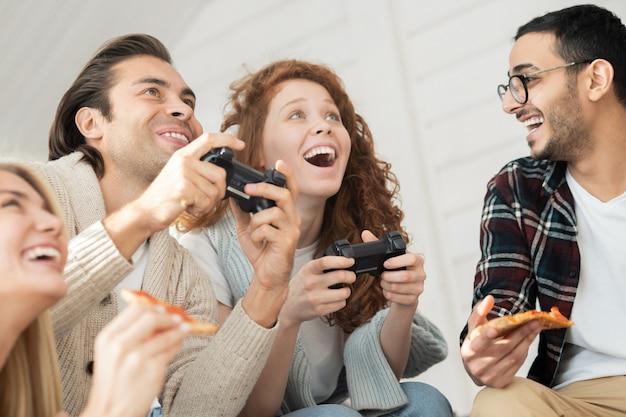 Vista inferior de un joven y una mujer emocionados que juegan videojuegos mientras sus amigos comen pizza y los apoyan