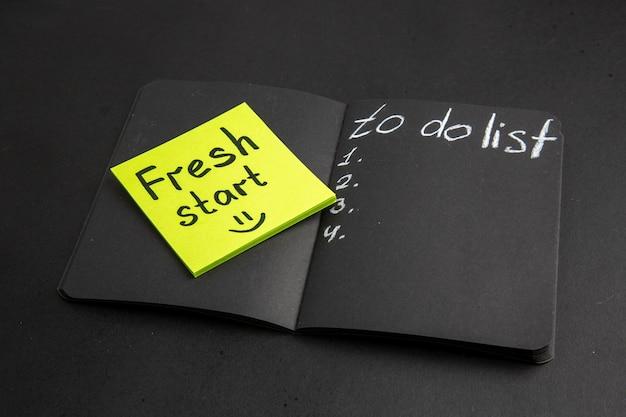 Vista inferior de la lista de tareas escritas en el bloc de notas negro nuevo comienzo escrito en una nota adhesiva sobre fondo negro