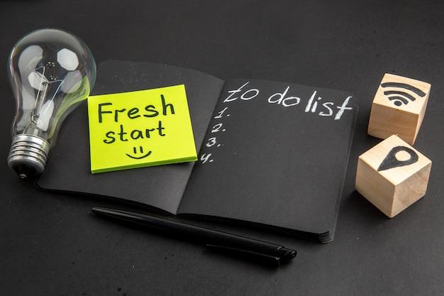 Vista inferior de la lista de tareas escritas en el bloc de notas negro nuevo comienzo escrito en la nota adhesiva wifi y los iconos de ubicación en cubos de madera, bolígrafo, bombilla de luz sobre fondo negro