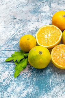 Vista inferior mandarinas frescas sobre superficie azul blanca
